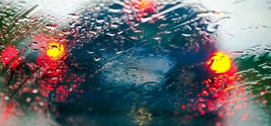En blå bil skymtas genom en regntäckt bilruta